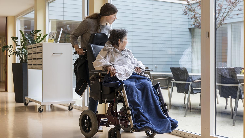 Mit Rollstuhl am Fenster