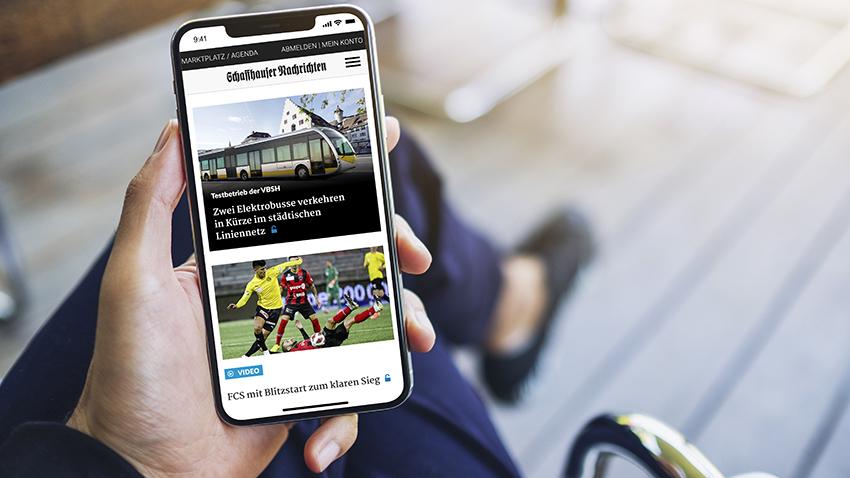 Nahaufnahme Hand mit Mobiltelefon mit Website der Schaffhauser Nachrichten
